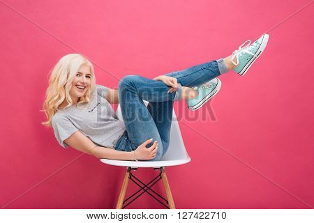 Smiling blonde woman sitting on the chair with raised legs over pink backgorund