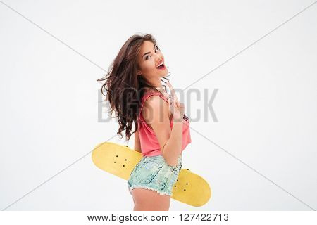 Cheerful woman with skateboard showing peace sign isolated on a white background