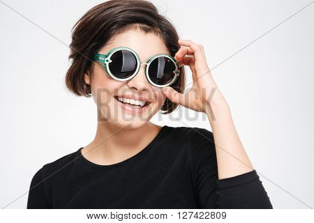 Smiling woman in sunglasses standing isolated on a white background