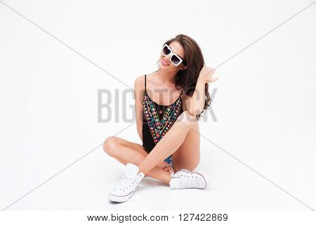 Happy cute woman sitting on the floor isolated on a white background