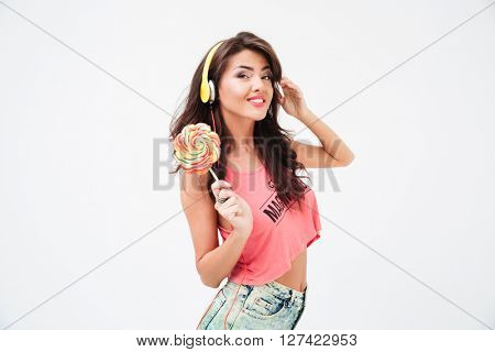 Smiling woman in headphones holding lollipop isolated on a white background