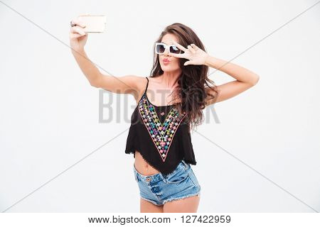 Stylish woman making selfie photo on smartphone isolated on a white background
