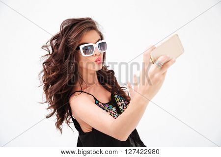 Fashion woman in sunglasses making selfie photo on smartphone isolated on a white background