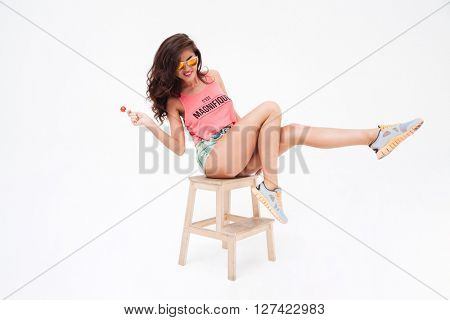 Full length portrait of a sexy woman in sunglasses and candy posing on the chair isolated on a white background