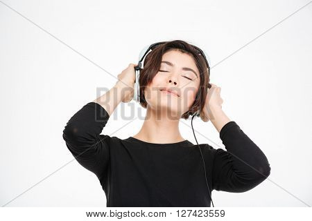 Pretty woman listening music in headphones isolated on a white background