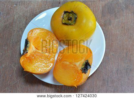 persimmon Chinese fruit half cut on dish