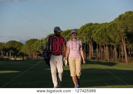 young couple walking to next hole on golf course. man carrying golf bag