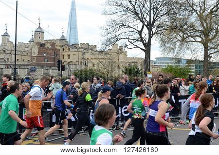 LONDON, UK, APRIL 24, 2016: The London Marathon -  Spectators running past the Tower of London with The Shard in the background