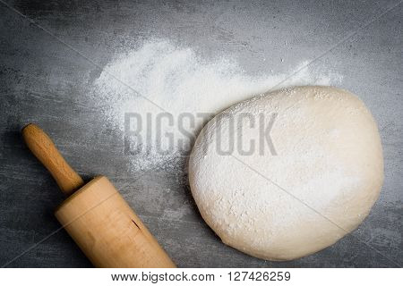 Dough, Flour And Rolling Pin On A Stone Table