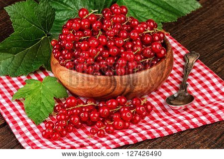 Ripe redcurrant decorated on a rustic background