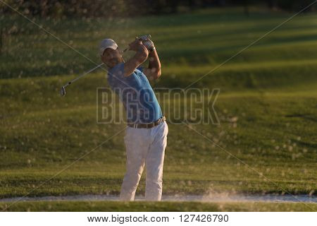 golfer shot ball from sand bunker at golf course with beautiful sunset in background