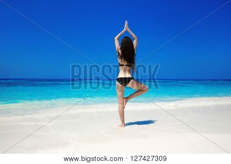 Woman Meditating In Tree Yoga Position On The Exotic Beach. Zen, Meditation, Peace. Balance. Young F
