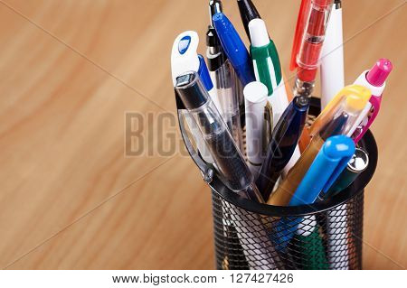 Metal holder with pens on the table