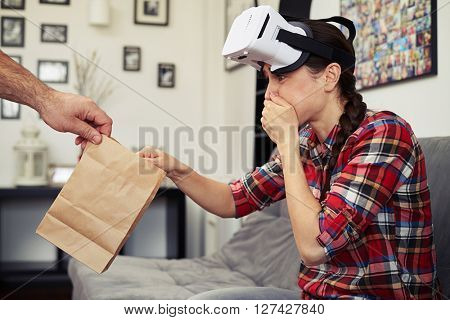 Woman sick after viewing virtual reality glasses, she takes a packet