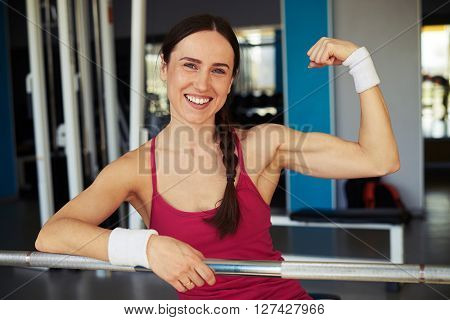 Smiling woman show her biceps in sport club and holding on to the rod in sport club