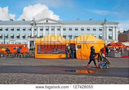 HELSINKI, FINLAND - APRIL 23, 2016: People in open air cafe on The Market Square near Gulf of Finland in the center of Helsinki. On the background is The City Hall.