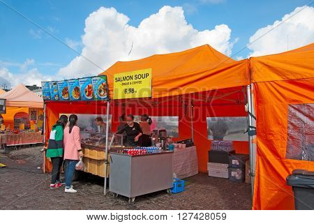 HELSINKI, FINLAND - APRIL 23, 2016: Tourists choose food in open air cafe on The Market Square near Gulf of Finland in the center of Helsinki
