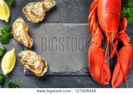 Fine selection of crustacean for dinner. Steamed lobster and oysters on dark background