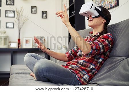 Woman pressing a button using virtual reality headset glasses and sitting on the couch