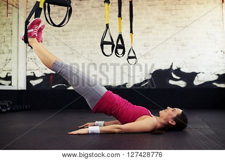 Smiling woman lying stretched using trx in sport club