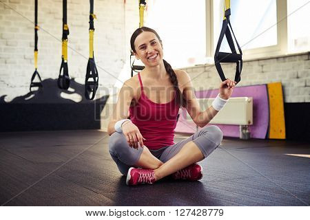 Young smiling girl in sportswear is sitting and holding trx