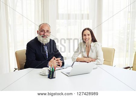 Portrait of smiling young businesswoman and senior man with beard in meeting