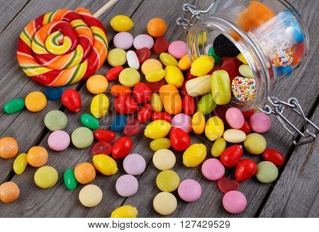 Colorful candies in jar on wooden table with copy space. Candies scattered on the wooden table