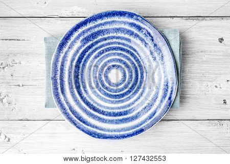 Blue and white ceramic plate on the white wooden table