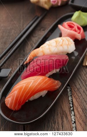Sushi Nigiri Set On A Black Plate Over Wooden Table