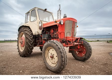 Old red russian tractor against a cloudy sky