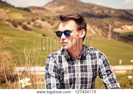 Young blond man portrait in the countryside.
