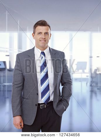 Portrait of happy caucasian businessman standing at business office, suit and tie, hands in pocket, smiling, looking at camera, copyspace.