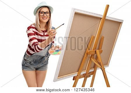 Young woman painting on a canvas and looking at the camera isolated on white background