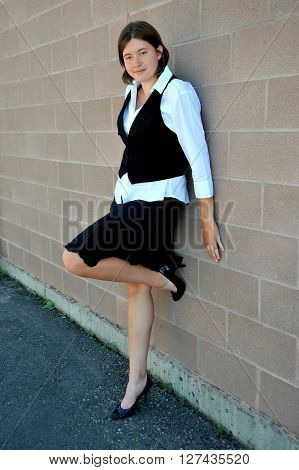 Female nanny in uniform standing against a wall outside.