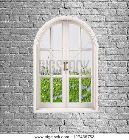 grey brick wall and white window with green grass and flowers over it