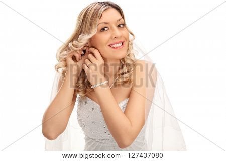 Young blond bride putting earrings on her ears and looking at the camera isolated on white background