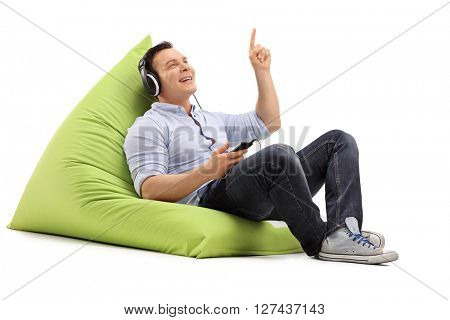 Young guy listening to music on headphones seated on a green beanbag isolated on white background
