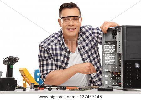 Young PC technician repairing a broken desktop computer and looking at the camera isolated on white background