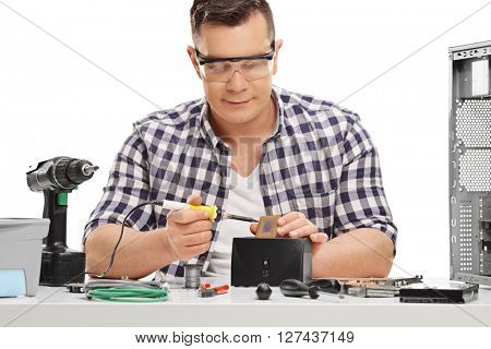 Young PC technician working with soldering iron and repairing a computer isolated on white background