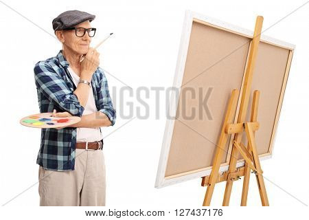 Studio shot of a senior painter looking at a painting isolated on white background