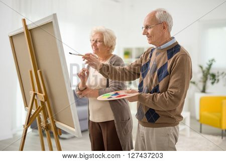 Older man and woman painting something on a canvas with paintbrushes at home