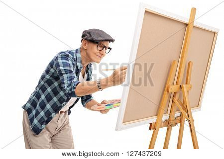 Senior painter painting on a canvas with a paintbrush isolated on white background