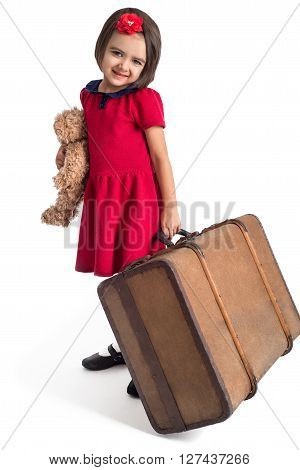 Beautiful little Girl smiling in red dress with suitcase and toy bear