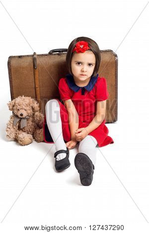 Unhappy beautiful little Girl in red dress with suitcase and toy bear