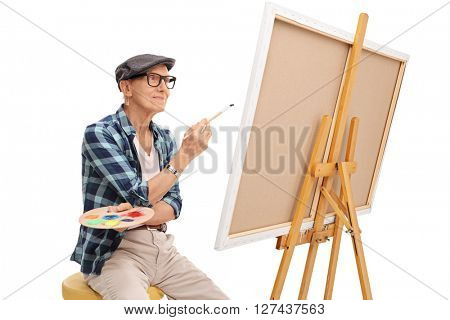 Senior artist looking at a painting seated on a chair isolated on white background
