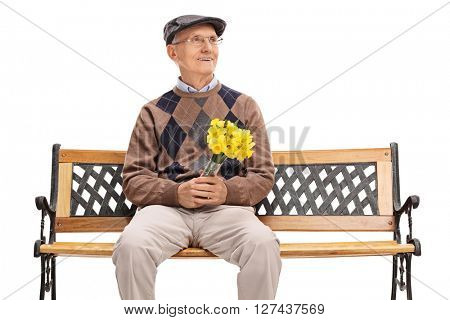 Senior gentleman waiting for his date seated on a bench and holding a bunch of flowers isolated on white background