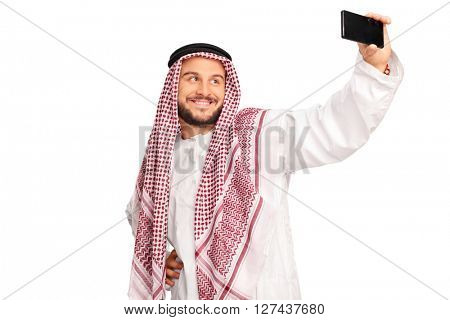 Modern Arab taking a selfie with cell phone and smiling isolated on white background