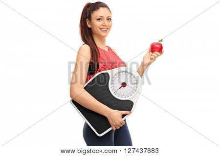 Young beautiful woman holding an apple and a weight scale isolated on white background