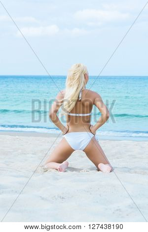 Beautiful and sporty woman in a swimsuit relaxing on a beach at summer