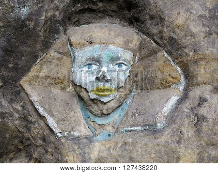 Rock relief - the face of the Sphinx - carved into the sandstone cliff, Czech republic